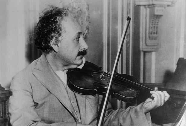 1931 --- El mundialmente famoso físico y profesor Albert Einstein se muestra sentado a bordo de la S. Belgenland, viajando desde Nueva York a San Diego. Aquí, él está sentado y tocando el violín para su ocio. --- Imagen de © Bettmann / CORBIS